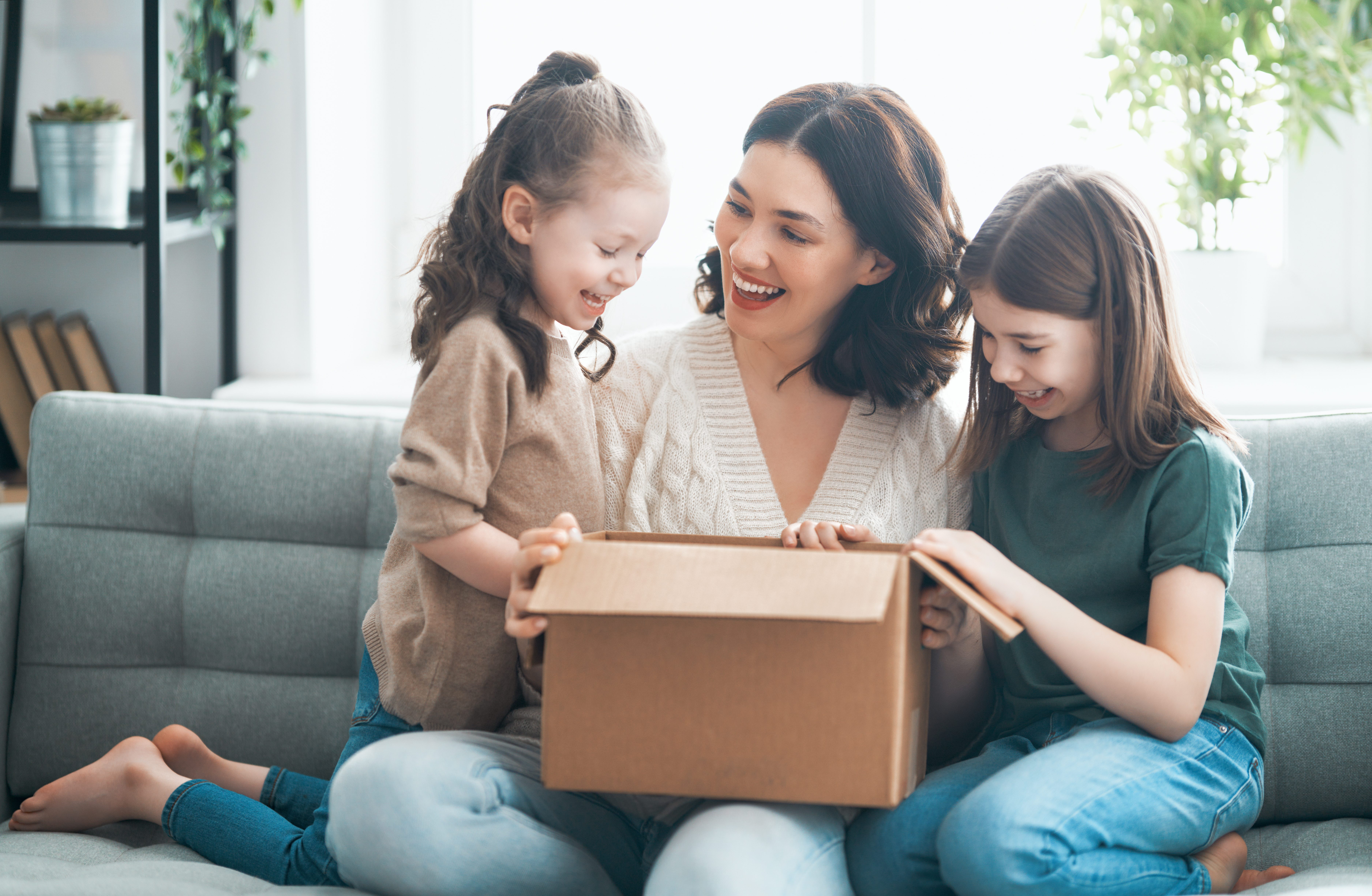 woman and two kids opening a box