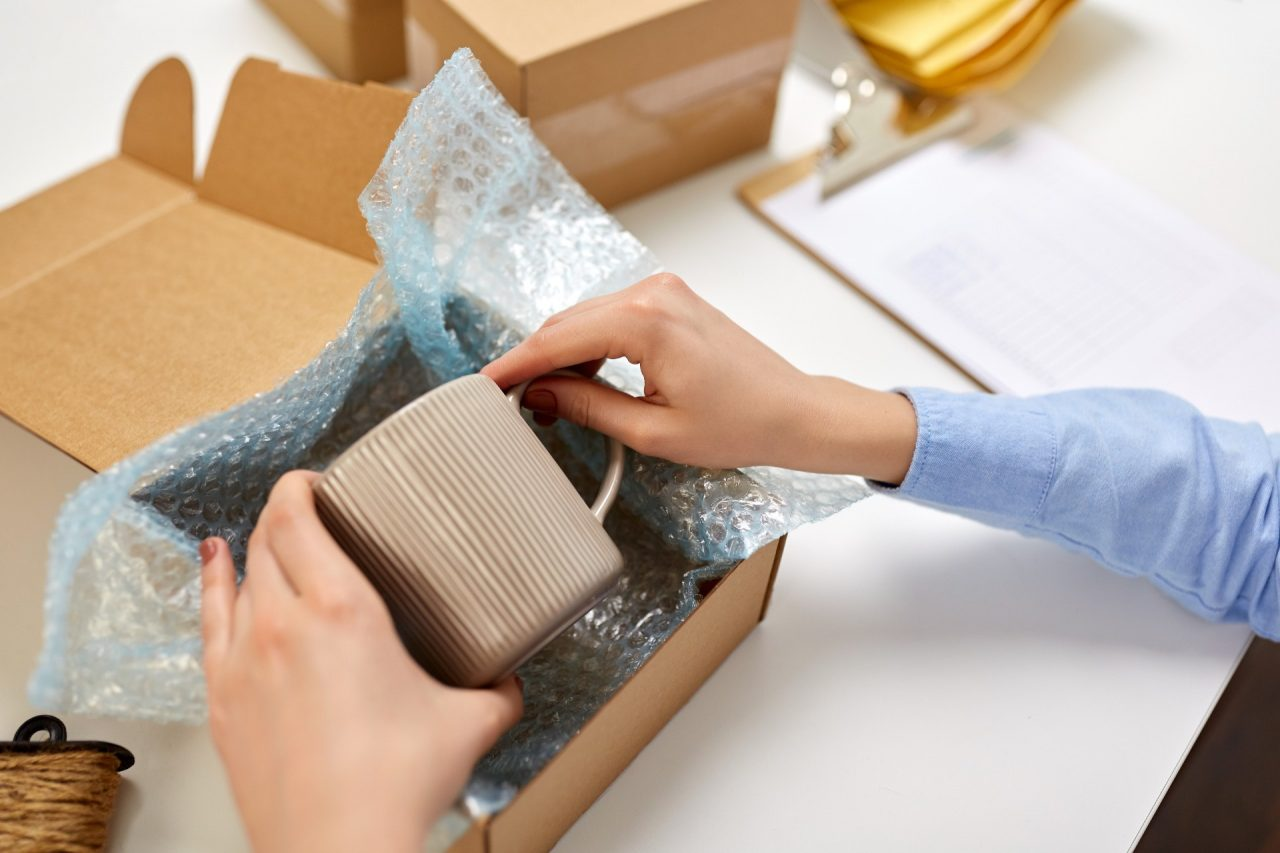 delivery, mail service, people and shipment concept - close up of female hands packing mug into parcel box and it wrapping into protective bubble wrap at post office